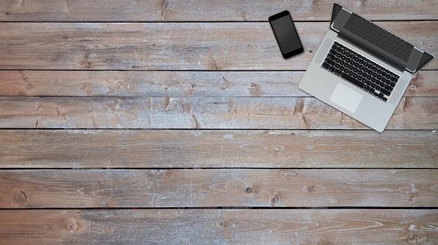 Πρόκειται για μια εικόνα με φόντο ένα ξύλινο ΄δπεδο με τοποθετημένο πάνω του ένα υπολογιστή και ένα κινητό τηλέφωνο