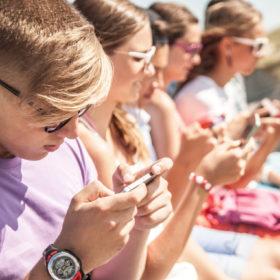 Η σελίδα έφηβοι παρουσιάζει μια εικόνα με μια μεγάλη παρέα εφήβων που είναι όλοι προσηλωμένοι στα κινητά τους τηλέφωνα.