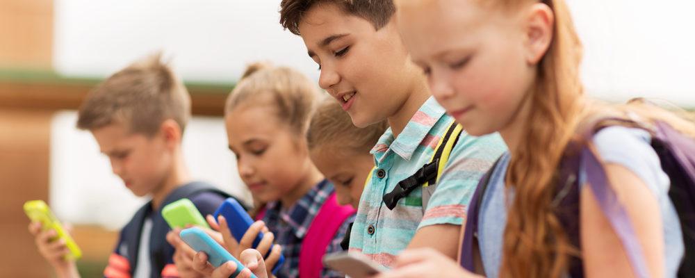 Απεικονίζεται μια όμορφη παιδική παρέα από αγοράκια και κοριτσάκια που έχουν όλα στραμμένη την προσοχή τους στα κινητά τηλέφωνα τους.